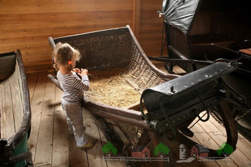 Девочка возле плетеных старых саней