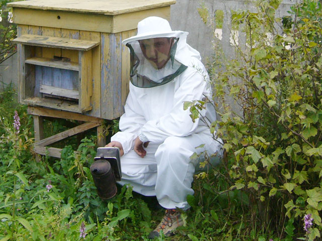 Молодой пчеловод в специальном костюме возле улья