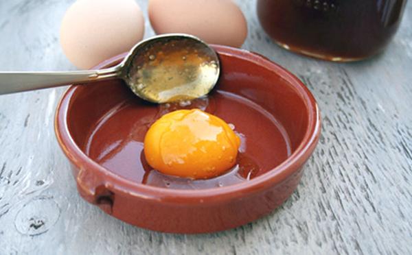 Куриное сырое яйцо в тарелке